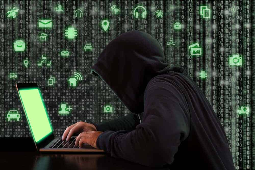 Cybersecurity image: Computer hacker hunched over a laptop computer.